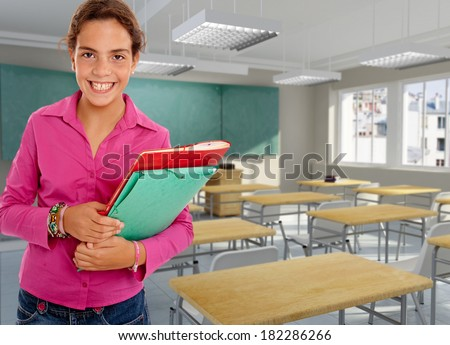 Smiling young girl holding a pair of files in a classroom - stock photo