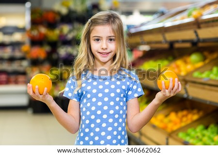 Smiling young girl holding oranges at supermarkey - stock photo