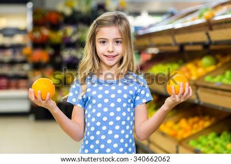 Smiling young girl holding oranges at supermarkey - stock photo