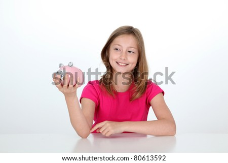 Smiling young girl holding piggy bank - stock photo
