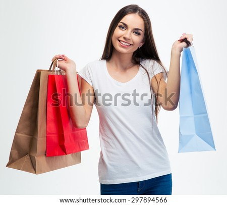 Smiling young girl holding shopping bags isolated on a white background. Looking at camera - stock photo