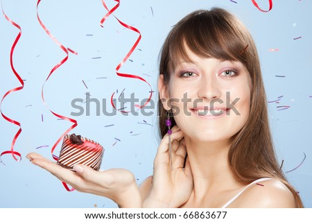 Smiling young girl holds cake with confetti and ribbons on background