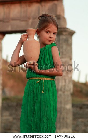 Smiling young girl in a vintage dress from the ancient Greek amphora on the excavation of the ancient city/Little Greek goddess on the ruins of the Greek city - stock photo