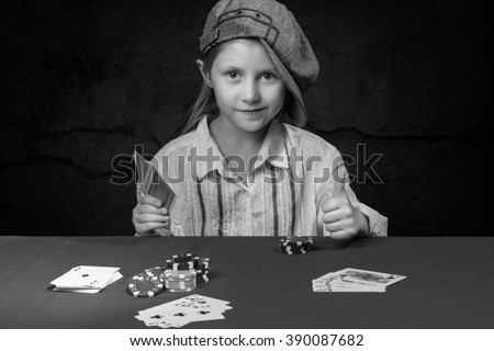 Smiling young girl in cap sitting at a poker table with cards in hand and shows lifted upwards thumb, black and white photo - stock photo