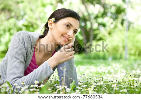 smiling young girl in spring park smelling flower - stock photo