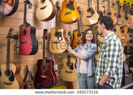 Smiling young girl is showing husband guitar in music store. - stock photo