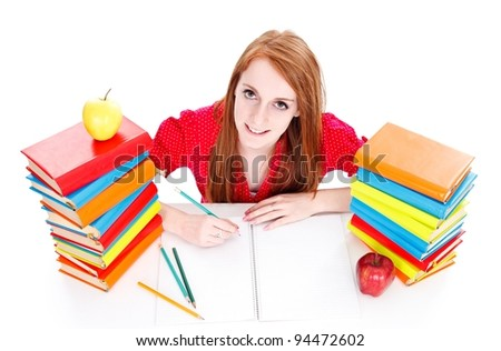 Smiling young girl learning between books with apple on them