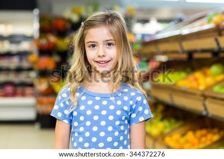 Smiling young girl looking at camera at supermarket - stock photo