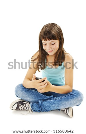 Smiling young girl reading sms on your cell phone. Isolated on white background - stock photo