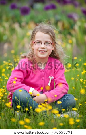 Smiling young girl sitting in the green - stock photo