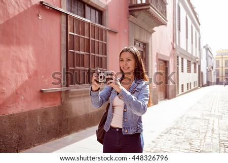 Smiling young girl taking a picture in a narrow paved street with old pink buildings behind her in casual jeans and denim jacket