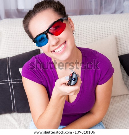 smiling young girl watching 3d television at home - stock photo