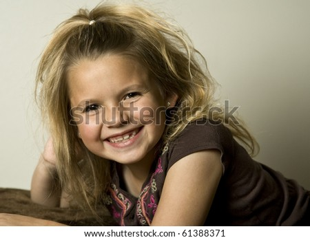 Smiling young girl wearing a brown shirt, looking at the viewer.