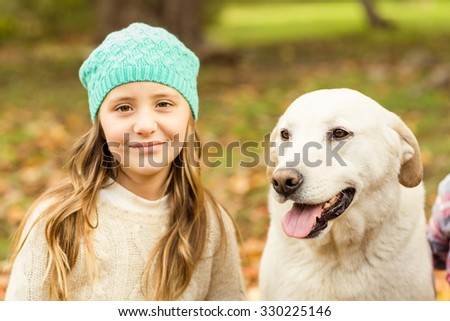 Smiling young girl with her dog on an autumns day