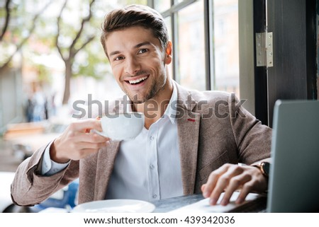Smiling young handsome businessman holding cup of coffee and working with laptop in cafe indoors - stock photo