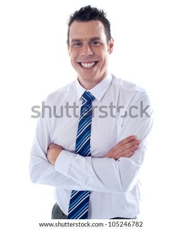 Smiling young handsome executive posing with folded arms - stock photo