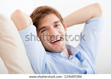 smiling young handsome man happy smile looking at camera relaxing and sitting on sofa at home - stock photo