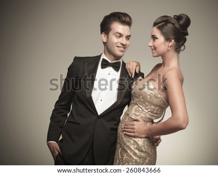 Smiling young handsome man looking at his wife while embracing her. - stock photo