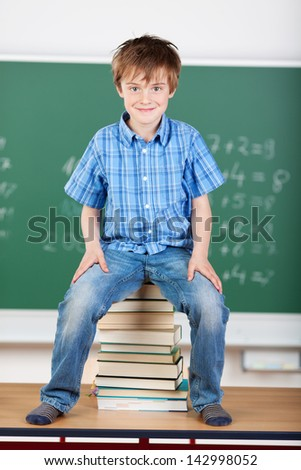 Smiling young handsome student sitting on a pile of books - stock photo