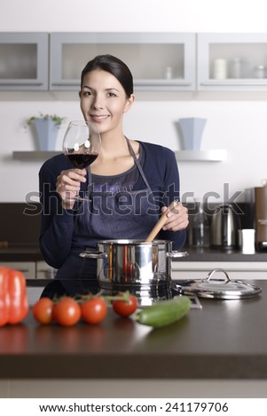 Smiling young housewife celebrating with red wine raising her glass to toast the camera as she stands at the stove in the kitchen preparing dinner - stock photo