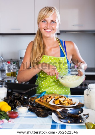 Smiling young housewife stuffing mollusc shells in kitchen