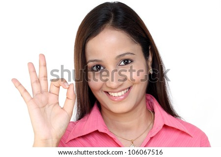 Smiling young Indian Business woman showing ok sign - stock photo