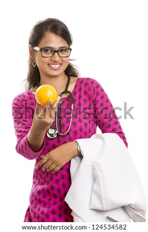 Smiling young Indian women doctor hand with orange - stock photo