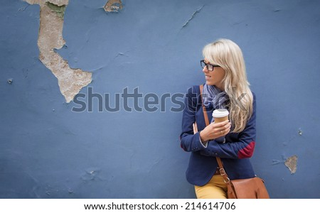 Smiling young lady standing at the wall outdoors and holding a cup of coffee. - stock photo