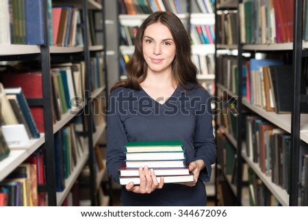 smiling young lady with loose dark blonde hair standing and holding a pile of books between book shelves in the library, looking in front of her, front view, a concept of studying