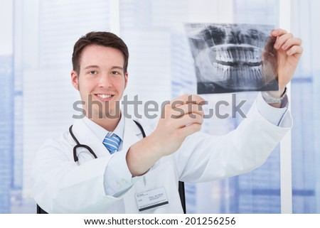 Smiling young male doctor examining dental X-ray in hospital - stock photo