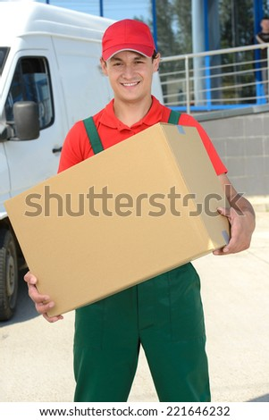 Smiling young male postal delivery courier man in front of cargo van delivering boxes