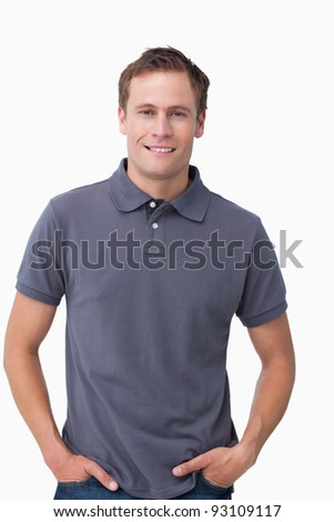 Smiling young male with hands in his pockets against a white background - stock photo