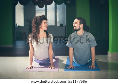 smiling young man and woman doing yoga  indoor healthy lifestyle concept