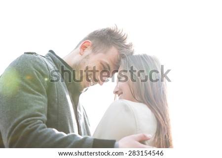 Smiling young man and woman embracing against clear sky - stock photo