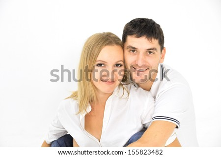 Smiling young man and woman sitting against white