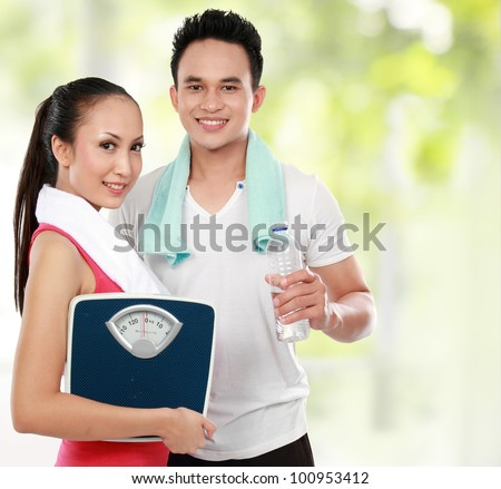 Smiling young man and woman with water and apple. diet fitness concept - stock photo