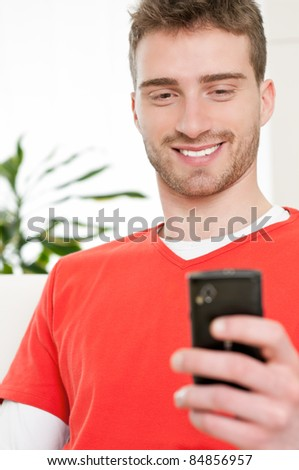 Smiling young man browsing and text messaging on his smart phone at home - stock photo