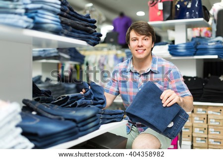 Smiling young man choosing new pair of blue jeans at the store - stock photo