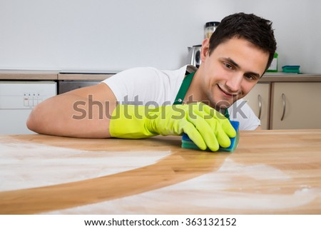 Smiling young man cleaning dust on wooden table with sponge at home - stock photo