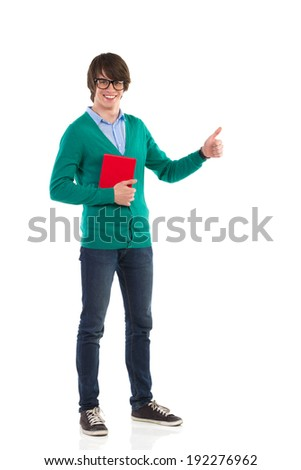 Smiling young man holding a book and showing thumb up. Full length studio shot isolated on white. - stock photo