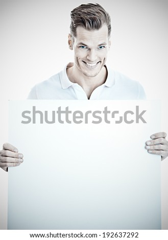 Smiling young man holding a placard ready for your text or product - stock photo