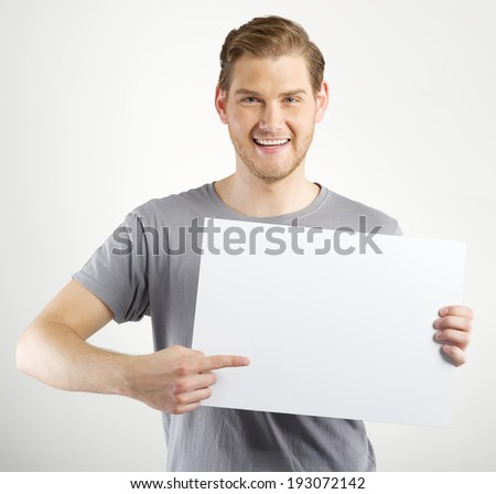 Smiling young man holding blank sign in hands - stock photo