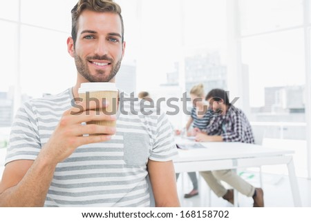 Smiling young man holding disposable coffee cup with colleagues in background at a creative bright office