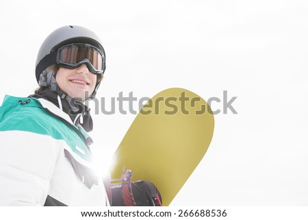 Smiling young man holding snowboard against clear sky - stock photo