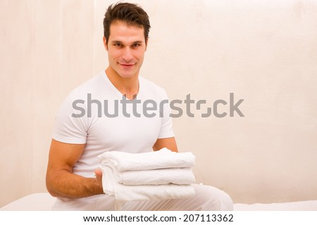 Smiling young man holding stack of towels - stock photo