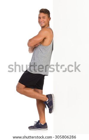 Smiling young man in sport clothes standing and leaning on a whit wall. Side view. Full length studio shot isolated on white.