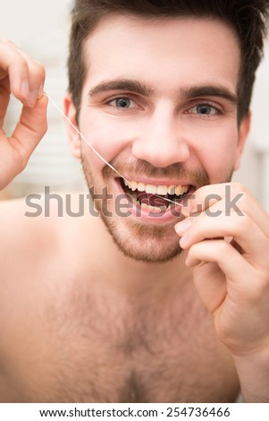 Smiling young man is cleaning teeth with dental floss. - stock photo