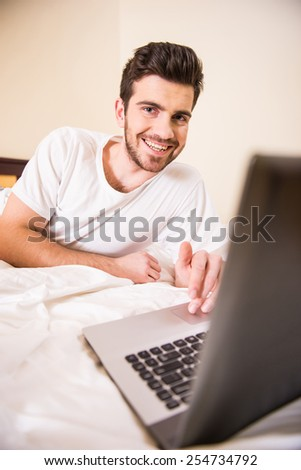 Smiling young man is working with laptop, lying on bed.