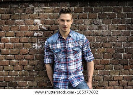 Smiling young man leaning on old brick wall, wearing blue and red shirt and jeans - stock photo