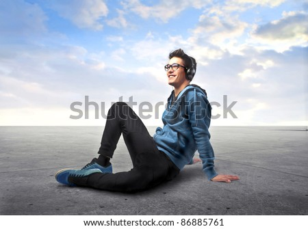 Smiling young man listening to music - stock photo